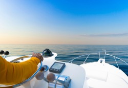 Hand of captain on steering wheel of motor boat in the blue ocean during the fishery day. Success fishing concept. Ocean yacht