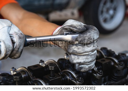 Hand of car mechanic adjusting an engine with socket wrench, Automotive repair service in workshop