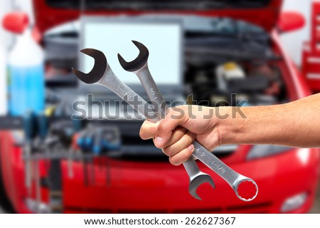 Hand of car mechanic with wrench. Auto repair garage. #262627367