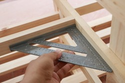 Hand of carpenter is measuring angle of wooden furniture