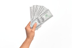 Hand of caucasian young man holding bunch of dollars banknotes over isolated white background