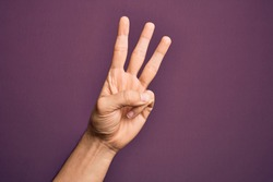 Hand of caucasian young man showing fingers over isolated purple background counting number 3 showing three fingers