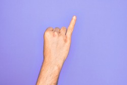 Hand of caucasian young man showing fingers over isolated purple background showing little finger as pinky promise commitment, number one