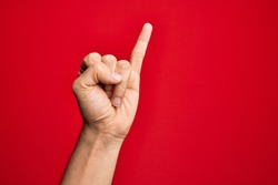 Hand of caucasian young man showing fingers over isolated red background showing little finger as pinky promise commitment, number one
