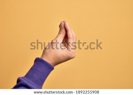 Hand of caucasian young man showing fingers over isolated yellow background doing Italian gesture with fingers together, communication gesture movement Stockfoto ©
