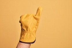 Hand of caucasian young man with gardener glove over isolated yellow background showing little finger as pinky promise commitment, number one
