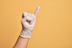 Hand of caucasian young man with medical glove over isolated yellow background showing little finger as pinky promise commitment, number one