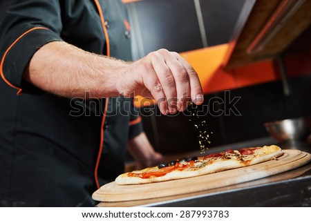 hand of chef baker in uniform adding spice into pizza after pizza preparation at restaurant kitchen