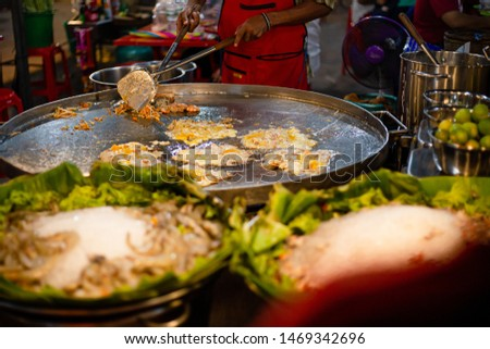 Hand of chef cooking Oysters fried in egg batter in hot flat pan,Cooking, Thailand, Bangkok, Omelet, Oyster,Oyster, Fried, Kitchen, Asia, Egg, Thailand, Asian and Indian Ethnicities, Commercial.