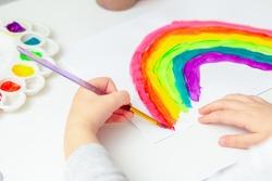 Hand of child painting rainbow during coronavirus pandemic.