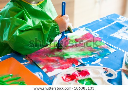 Hand of child painting with roller