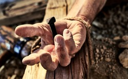 Hand of Christ nailed to the cross with a close up view of a mans hand with an iron nail hammered through onto a wooden cross symbolic of the crucifixion of Christ at Easter