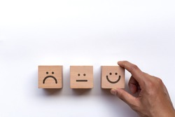 Hand of client show a feedback with smile face wood cube. Service rating, satisfaction concept