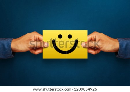 Hand of client show a feedback with smiley face card. Service rating, satisfaction concept #1209854926