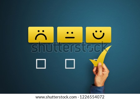 Hand of client show a feedback with smiling face card. Service rating, satisfaction concept #1226554072