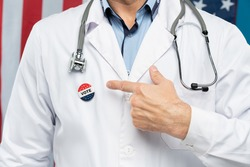Hand of contemporary American citizen in doctor uniform pointing at insignia on his chest meaning to say that he is going to vote