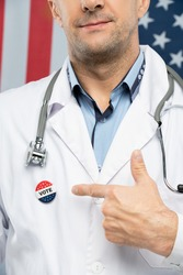 Hand of contemporary mature American clinician in whitecoat pointing at insignia on his chest meaning that he is going to vote