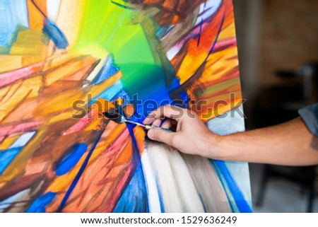 Hand of contemporary painter with special instrument mixing colors on paper while working over abstract painting #1529636249