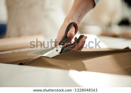 Hand of contemporary tailor or seamstress with scissors cutting piece of brown fabric on table in tailoring shop