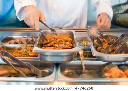 hand of cook takes nippers fried meat in lunch counter at public catering restaurant - stock photo