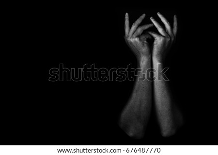 hand of depressed and hopeless man alone in the dark, white tone