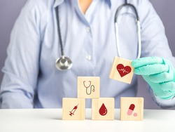 Hand of doctor arranging wood blocks with healthcare medical icons. Space for text. Health and medical concept.
