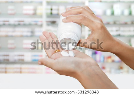 Shutterstock hand of doctor holding medicine bottle on medicine cabinet and store medicine and pharmacy drugstore