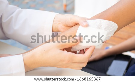 hand of Doctor is using clean cotton dressing infection wound at a women arm. Bandage for wound dressing at a clinic. medical care healthcare insurance concept. Foto d'archivio ©
