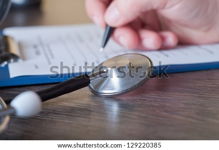 Hand of doctor with pen writing on prescription blank