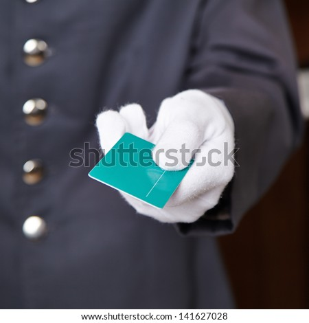 Hand of doorman giving key card to hotel room