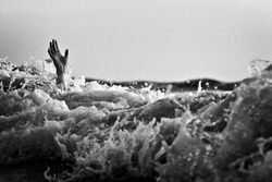 Hand of drowning man trying to swim out of the stormy ocean. Black and white photo.