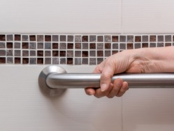 hand of elderly woman holding aluminium rail in toilet. Close up view.