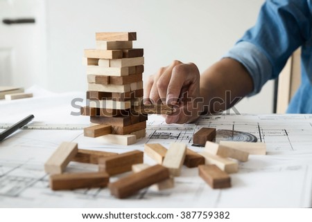 Hand of engineer playing a blocks wood game (jenga) on blueprint or architectural project.