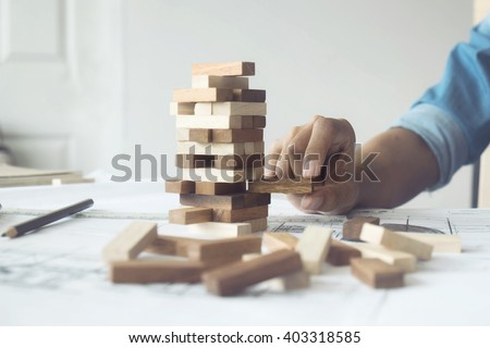 Hand of engineer playing a blocks wood game (jenga) on blueprint or architectural project vintage tone.