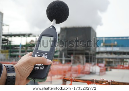 Hand of Environmental officer holding to use sound level meter for monitor is part of the prevention of environmental impacts at Chemical plant area or refinery factory. Stock photo ©