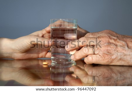 hand of grandmother and women with a pill