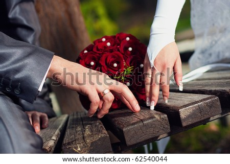 Hand of  groom and  bride with  rings near wedding bouquet