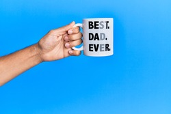 Hand of hispanic man holding best dad ever coffee cup over isolated blue background.