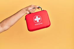 Hand of hispanic man holding first aid kit over isolated yellow background.