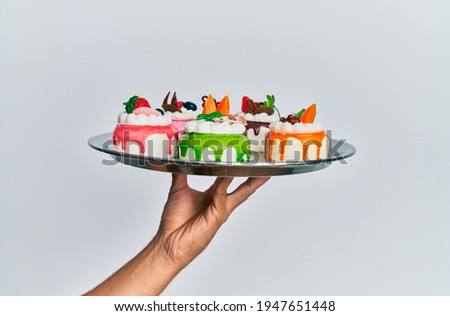 Hand of hispanic man holding tray with cake slices over isolated white background. Foto stock ©