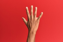 Hand of hispanic man over red isolated background counting number 5 showing five fingers