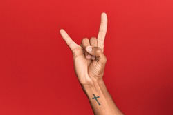 Hand of hispanic man over red isolated background gesturing rock and roll symbol, showing obscene horns gesture
