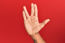 Hand of hispanic man over red isolated background greeting doing vulcan salute, showing hand palm and fingers, freak culture