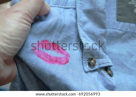 Hand of housewife holding husband shirt,found lipstick marks on his collar. #692056993