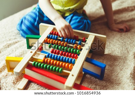 Hand of little boy playing with abacus. Clouse up picture of curly cute toddler playing with wooden toy. Children education. Preschooler baby learns to count.