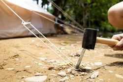 Hand of male holding a rubber mallet,hammering aluminium steel tent stakes pegs nail,fastening tent for camping,hit or beat anchor of the tent into the ground,hammer with rubber head, wooden handle