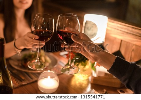 Hand of man and woman sitting in a dark restaurant by a table and holding glasses with red wine