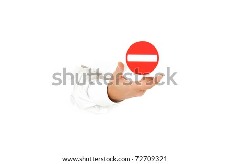 "Hand of man breaking through a paper wall and showing ""no entry""  forbidden access sign. Copy space. Studio shot. White background."
