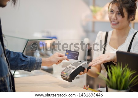 Hand of man customer using wireless or contactless payment of a credit card. Young Asian cashier or seller are smiling to accept payment by nfc technology at retail shop. Contactless payment concept.