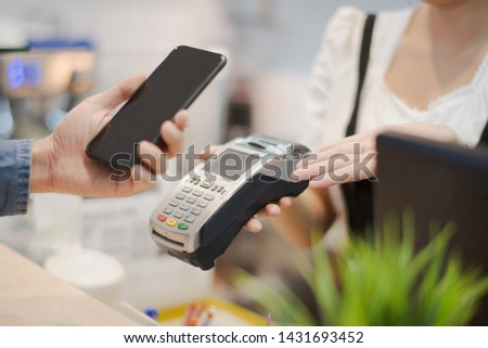 Hand of man customer using wireless or contactless payment of a smart phone. Young Asian cashier or seller are smiling to accept payment by nfc technology at retail shop. Contactless payment concept.